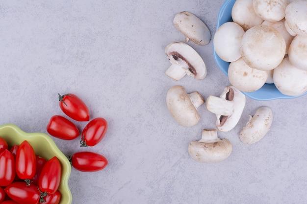 Kirschtomaten und pilze auf grau.