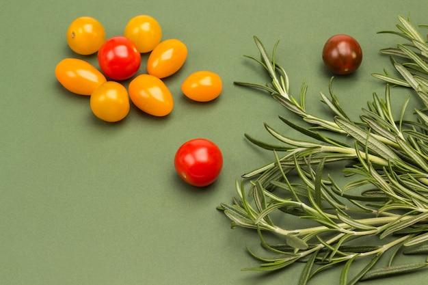 Kirschtomaten und rosmarin auf grüner oberfläche