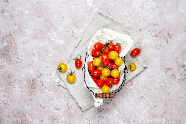 Kirschtomaten von verschiedenen farb-, gelben und rotenkirschtomaten in einem korb auf hellem hintergrund