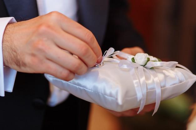 Kissen mit eheringen. bräutigam, der ring während der zeremonie nimmt
