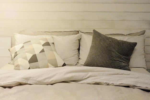 Kissen und decke auf bett im weinlese-hölzernen schlafzimmer mit der beleuchtung der oberen linken seite.