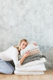 Kissenkomfort. qualität bettwäsche gemütlichkeit. junge frau, die auf kissenhaufen schläft.
