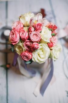 Kiste mit weissem und orangenem bouquet steht auf floristenarbeit ta