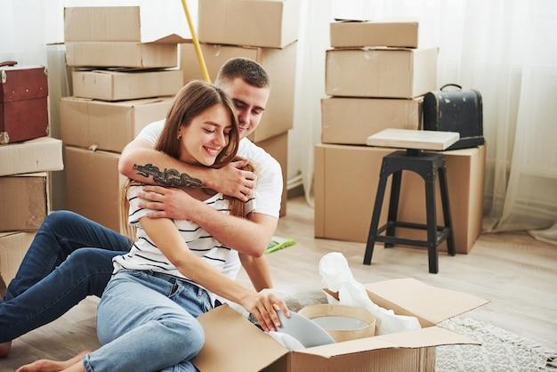 Kisten auspacken. fröhliches junges paar in ihrer neuen wohnung. konzeption des umzugs.