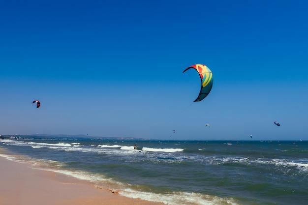 Kitesurfen auf den wellen des meeres am strand an einem sonnigen tag
