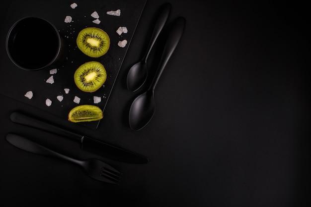 Kiwi auf einem schwarzen hintergrund mit schwarzem glas, schwarzblech, schwarzes tischbesteck, draufsicht