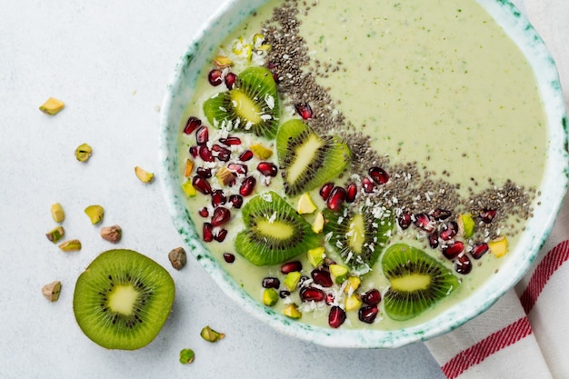Kiwi-bananen-smoothies-schüssel mit haferflocken, pistazien, granatapfelkernen und chia auf hellgrauem steinhintergrund