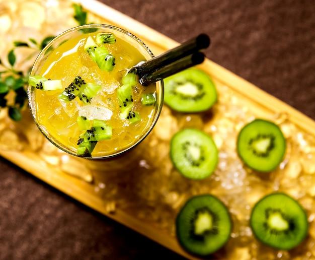 Kiwi-cocktail auf der holzbrett-zitronenzucker-syrop-eis-draufsicht