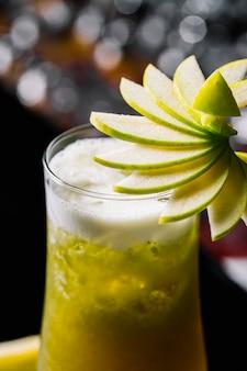Kiwi-cocktail von der seite mit apfel im glas