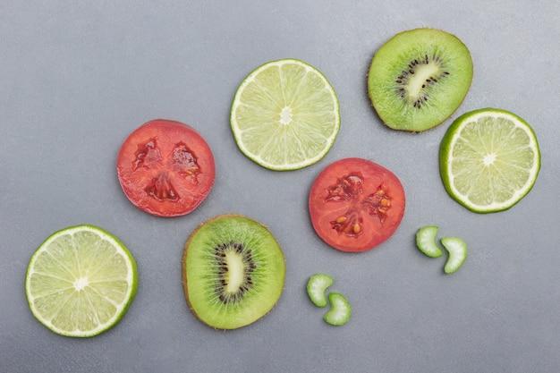 Kiwi-, limetten- und tomatenfruchtscheiben auf grauer oberfläche
