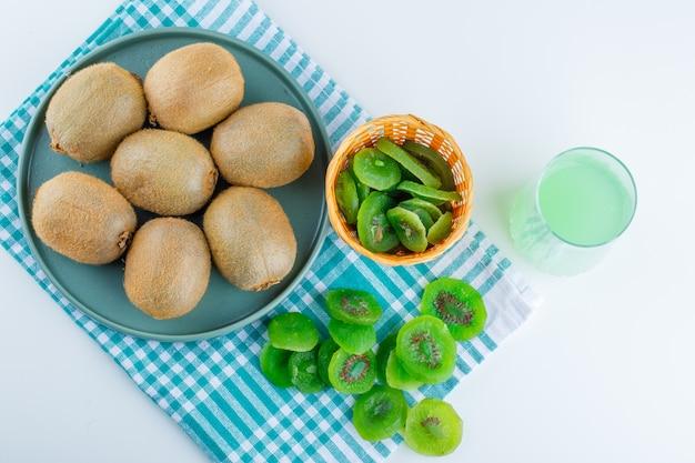 Kiwi mit getrockneter kiwi, trinken in einem teller auf weißem und picknicktuchhintergrund, draufsicht.