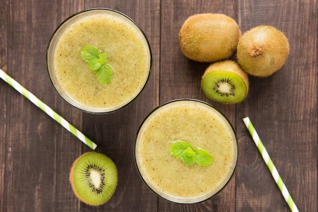 Kiwi smoothie mit frischen früchten auf hölzernem hintergrund. ansicht von oben