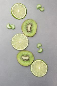 Kiwi- und limettenfruchtscheiben auf grauer oberfläche