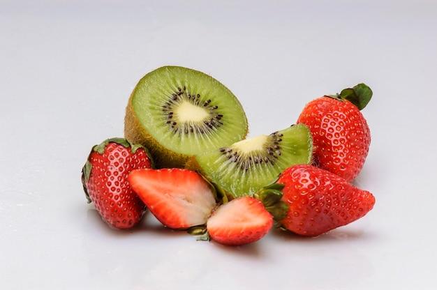 Kiwis und erdbeeren auf weißem hintergrund
