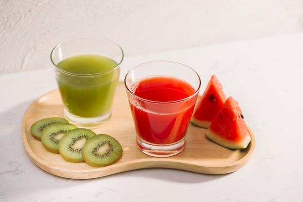 Kiwisaft und wassermelone mit fruchtscheiben auf holztablett