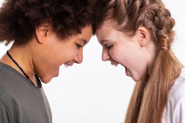 Klären sie beziehungen auf. emotionale und ausdrucksstarke kinder, die sich aneinander lehnen und laut schreien