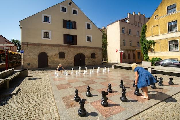 Klaipeda, litauen junge fröhliche frau spielt zusammen mit einem kleinen mädchen in großen schach