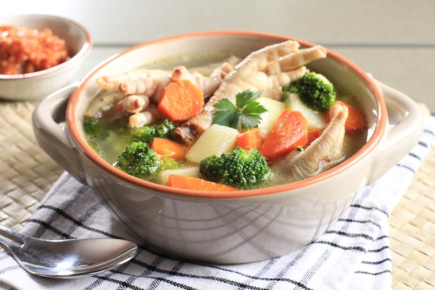 Klare hühnerfüße (klauen) suppe mit kartoffeln, brokkoli und karotten. serviert auf holztisch in brauner schüssel mit sambal