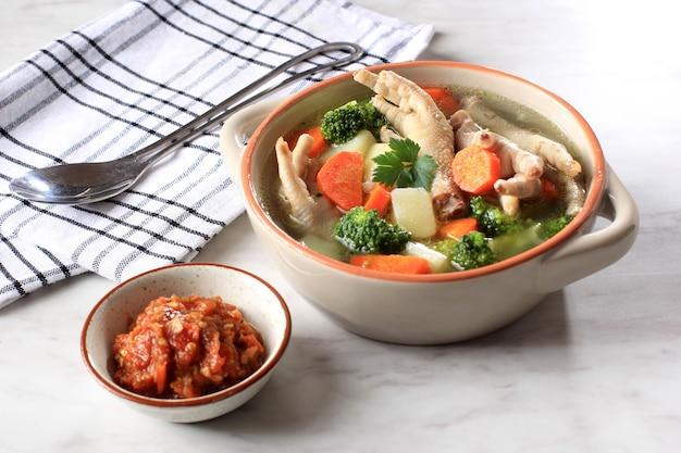 Klare hühnerfüße (klauen) suppe mit kartoffeln, brokkoli und karotten. serviert auf marmortisch in brauner schüssel mit sambal