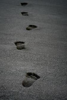 Klare menschliche fußabdrücke auf schwarzem sand vor der küste