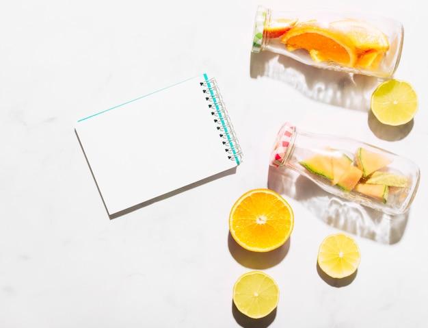 Klare notebook limette orange und glasflaschen mit geschnittenen zitrusfrüchten