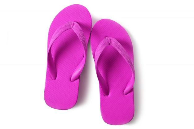 Klare rosa flipflops setzen die sandalen auf den strand, die auf weißem hintergrund lokalisiert werden