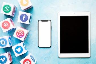 Klare Social Media-Blöcke mit Mobiltelefon und digitaler Tablette auf Blau malten Wand