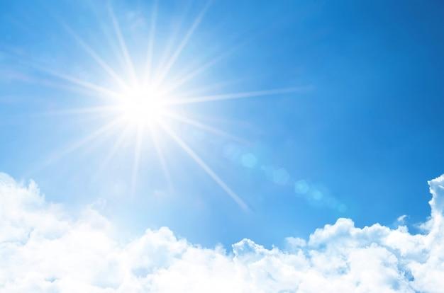 Klarer himmel mit strahlender sonne und strahlen in der atmosphäre, darunter leichte, flauschige wolken.
