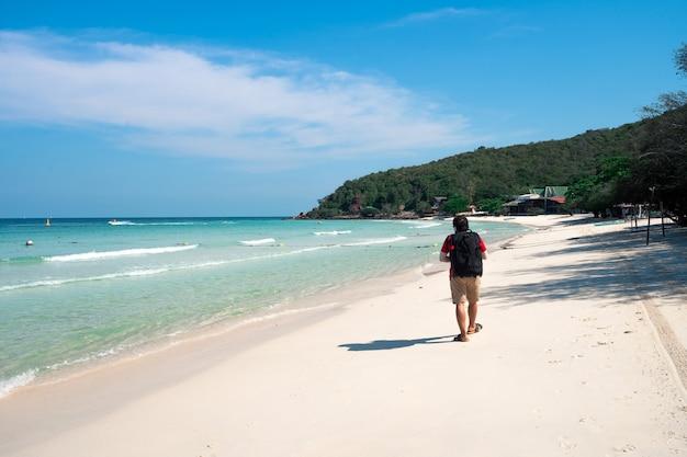 Klares blaues meer, weißer sandstrand am tag des klaren himmels auf der berginsel mit backpacker-mann, der auf sand geht, thian-strand auf der insel koh larn, reiseziel in chonburi, thailand
