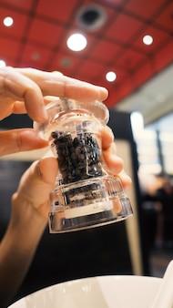 Klares farbglas und thailändische schwarze pfeffermühle oder mühle in den händen, die die flasche verdrehen