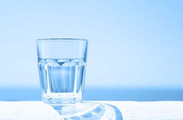 Klares wasser in einem transparenten glas vor dem hintergrund des meeres. gesundes lebensstilkonzept.
