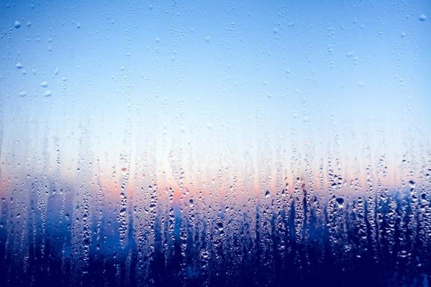 Klares wasser tropft auf das glasfenster.