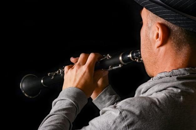 Klarinette in den händen eines mannes auf einer schwarzen oberfläche
