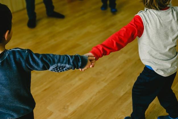 Klasse der musik in der schule mit den kindern und lehrern, die händchenhalten tanzen
