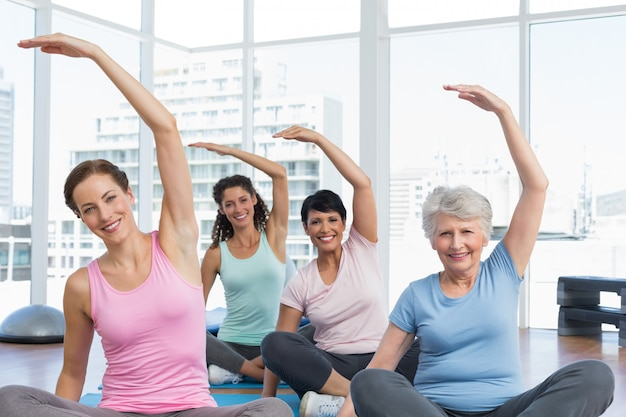 Klasse, die hände an der yogaklasse ausdehnt