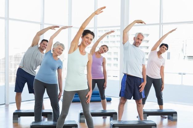 Klasse, die hände in der yogaklasse ausdehnt Premium Fotos