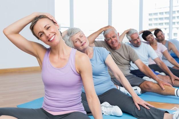 Klasse, die hals in der reihe an der yogaklasse ausdehnt