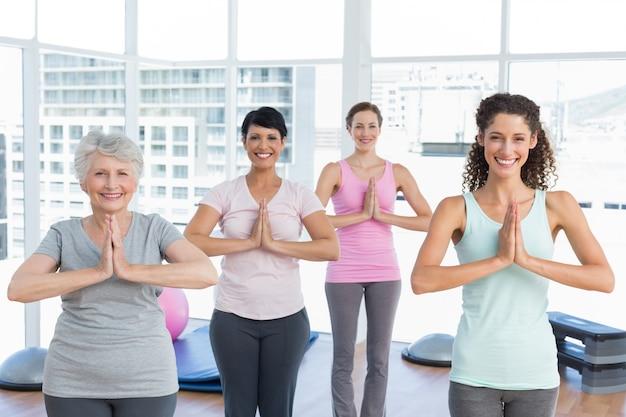 Klasse, die in namaste haltung an der yogaklasse steht