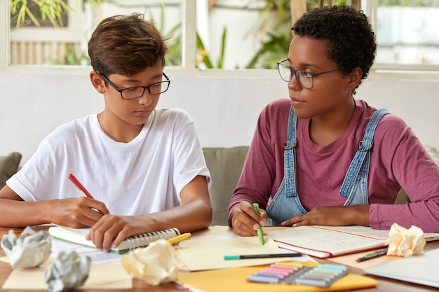 Klassenkameraden gemischter rassen lernen zusammen, schreiben in ein notizbuch, schreiben informationen aus papieren um, bereiten sich auf die schulprüfung vor, tragen freizeitkleidung, posieren am desktop, verbringen zeit miteinander. menschen, hilfskonzept