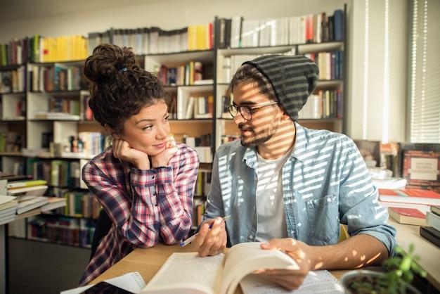Klassenkameraden lernen zusammen für prüfungen in der bibliothek. männlicher student, der seinem freund erklärt, wie man ein problem löst.