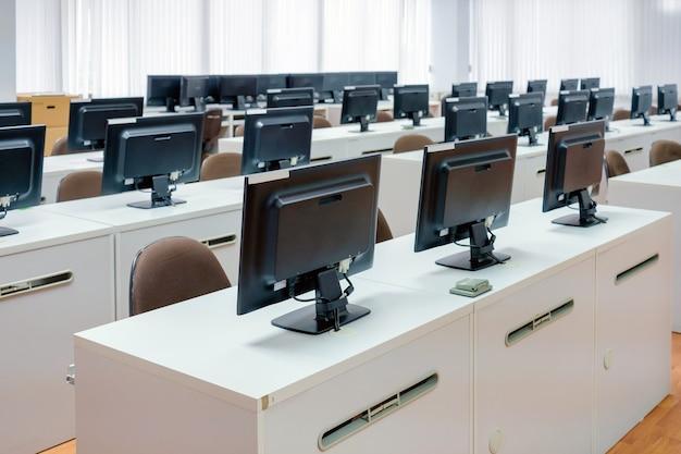 Klassenzimmer-computer. leeren sie keine leute mit viel monitorcomputer auf weißem schreibtisch.
