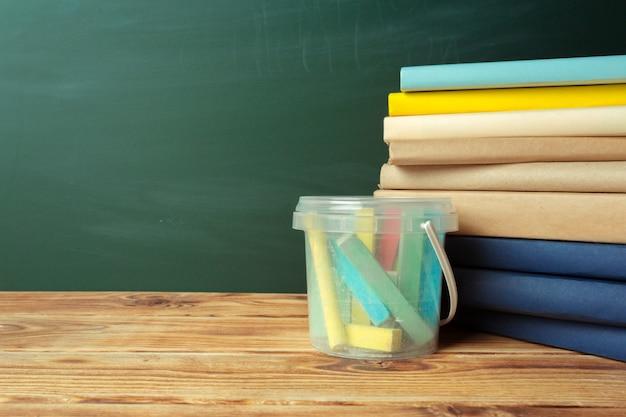 Klassenzimmer mit tafel, holztisch und büchern