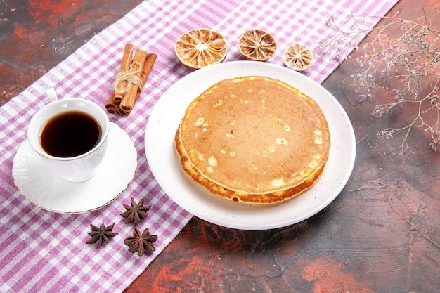 Klassische amerikanische leckere pfannkuchen auf einem rosa abgestreiften handtuch und tee auf gemischter farbe
