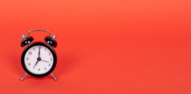 Klassische analoguhr mit glocken. auf rotem hintergrund isoliert. speicherplatz kopieren.