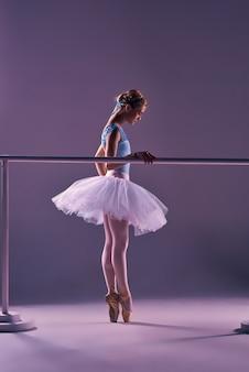 Klassische ballerina, die am ballett barre aufwirft