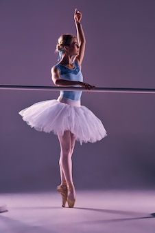 Klassische ballerina, die an der ballettbarre aufwirft