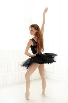 Klassische ballerinafrau im schwarzen kleid, das für den schwarzen schwan übt