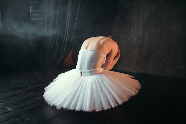Klassische balletttänzerin im weißen kleid sitzend auf theaterbühne, rückansicht. ballerina-training in der klasse auf schwarz