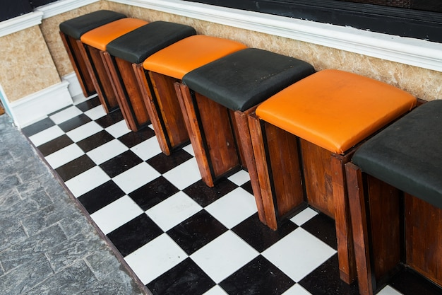 Klassische barhocker aus holz sind an einer bar im freien aufgestellt.