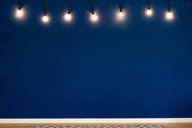 Klassische blaue wand mit hängenden glühbirnen, modernes rauminterieur